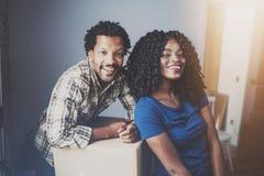 Vue de plan rapproché de jeune homme d'africain noir et de ses boîtes mobiles d'amie dans la nouvelle maison ensemble et faisant  Images libres de droits