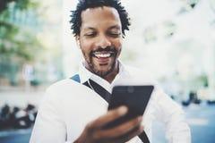 Vue de plan rapproché de l'homme africain américain heureux à l'aide du smartphone extérieur à textoter un message de sms avec de Images libres de droits