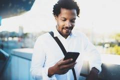 Vue de plan rapproché de l'homme africain de sourire heureux à l'aide du smartphone extérieur Portrait de jeune textoter gai noir Photographie stock