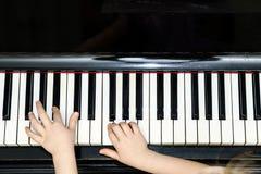 Vue de plan rapproché des mains de la fille et du clavier de piano Image stock