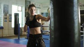Vue de plan rapproché du kickboxer femelle caucasien frappant le sac de sable avec ses mains et jambes dans seul le gymnase dur banque de vidéos