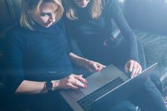 Vue de plan rapproché du processus coworking dans un bureau ensoleillé Deux jeunes filles travaillant sur l'ordinateur et à l'aid Photographie stock