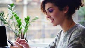 Vue de plan rapproché de la belle jeune femme à l'aide de son téléphone portable dans le café et le sourire Femme employant l'APP banque de vidéos