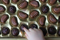 Vue de plan rapproché de la boîte de chocolats l'enfant prend la sucrerie photos stock