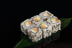 Vue de plan rapproché de petit pain japonais de tempura de crevette de sushi sur la feuille de banane au fond noir photographie stock