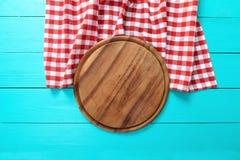 Vue de planche à découper ronde et de nappe rouge de plaid Fond en bois bleu dans le café Vue supérieure Images stock