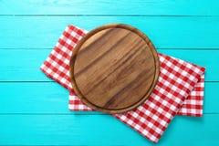 Vue de planche à découper ronde et de nappe rouge de plaid Fond en bois bleu dans le café Vue supérieure Image stock