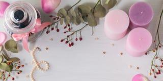 Vue de pot pour les biscuits, le collier de perle et trois bougies roses sur le fond clair Dogrose et branches d'evkalipt Photos libres de droits