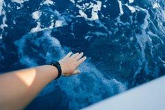 Vue de POV de portée de main aux vagues d'eau du bateau photographie stock