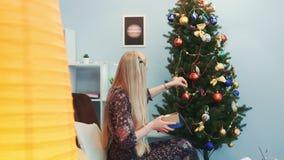 Vue de profil des jouets accrochants de gentille dame sur l'arbre de Noël banque de vidéos
