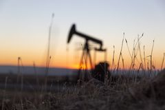 Vue de Pumpjack au coucher du soleil de la région de pétrole photographie stock