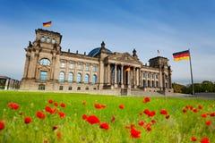 Vue de Reichstag avec les tulipes rouges et les drapeaux allemands Photo stock