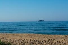 Vue de rivage sur le bateau simple à l'ancrage photo libre de droits