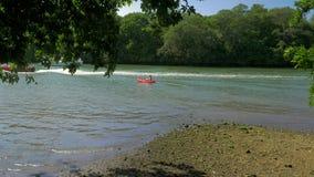 Vue de rivière avec l'homme dans le canoë et des canots automobiles banque de vidéos