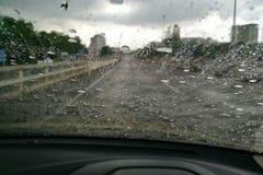 Vue de route par la fenêtre de voiture trouble avec la forte pluie, conduisant sous la pluie, temps pluvieux Photos stock