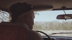 Vue de secousse d'angle arrière de vieil homme conduisant dans la rétro voiture à la route non-urbaine banque de vidéos