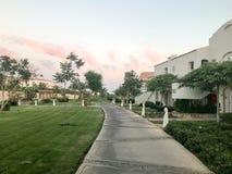 Vue de soirée du chemin en pierre et de la blancheur musulmane Arabe du bâtiment, des cottages parmi le vert tropical des palmier photographie stock
