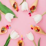 Vue de sucrerie lumineuse colorée en cônes de gaufre et fleurs blanches sur le fond rose Configuration plate, vue supérieure Photographie stock libre de droits