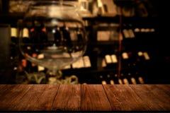 Vue de table en bois foncée sur une cuisine brouillée avec des bouteilles de images stock