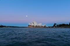 Vue de théatre de l'opéra de Sydney avec la pleine lune au coucher du soleil Photo stock