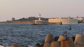 Vue de tir de laps de temps du phare blanc de l'autre côté du littoral au coucher du soleil banque de vidéos