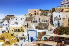 Vue de ville d'Oia avec les bâtiments, les touristes, les cafés et les boutiques blancs Santorini Photos stock