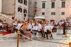 Vue de ville des personnes dans la vieille ville à la place regardant des musiciens tenant un concert extérieur libre dans Dubrov images libres de droits