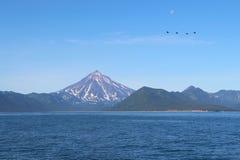 Vue de volcan de Vilyuchinsky et de x28 ; a également appelé Vilyuchik& x29 ; de l'eau La lune est évidente dans le ciel photos libres de droits