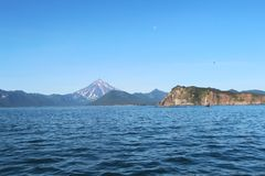 Vue de volcan de Vilyuchinsky et de x28 ; a également appelé Vilyuchik& x29 ; de l'eau La lune est évidente dans le ciel photographie stock