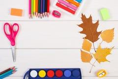 Vue des accessoires pour l'éducation et les feuilles automnales sur les conseils blancs, de nouveau au concept d'école Images libres de droits