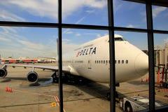 Vue des avions de delta par la fenêtre à l'aéroport Photographie stock
