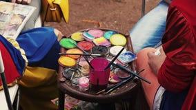 Vue des beaucoup colorant et brosses colorés Filles en peinture de costume Festival d'été banque de vidéos