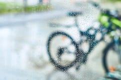 Vue des bicyclettes garées par le verre avec des gouttes de l'eau photos stock