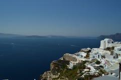 Vue des Chambres avec le dessus de toit sauté bleu avec la vue de la mer Égée bleuâtre en île de Santorini de ville d'Oia Archite photographie stock