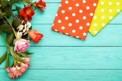 Vue des fleurs et des serviettes dans des points de polka sur le fond en bois bleu Vue supérieure et foyer sélectif Copiez l'espa Images stock