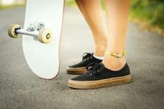 Vue des jambes d'une fille avec une planche à roulettes sur la rue Photographie stock libre de droits