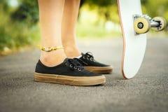 Vue des jambes d'une fille avec une planche à roulettes sur la rue Images stock