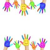 Vue des mains colorées peintes avec les visages de sourire. Photo stock