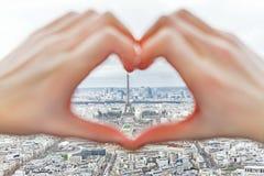 Vue des mains de coeur de Tour Eiffel et d'amour Image stock