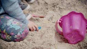 Vue des mains du ` un s de fille dans un bac à sable banque de vidéos