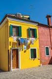 Vue des maisons colorées et des vêtements en terrasse accrochant dans une allée de Burano Photographie stock libre de droits