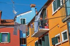 Vue des maisons, du balcon coloré et des vêtements en terrasse accrochant dans une allée dans Burano Image libre de droits