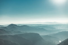 Vue des montagnes de Montserrat de matin avec le ciel de brume et de sarcelle d'hiver Photographie stock libre de droits
