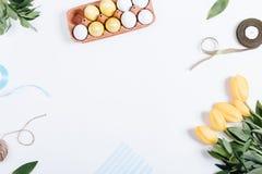 Vue des oeufs de pâques, des fleurs jaunes, des boîtes de cadeaux et des rubans Photographie stock libre de droits