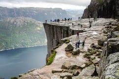 Vue des personnes marchant sur la roche de pupitre de Preikestolen de la distance avec un fjord dessous images libres de droits