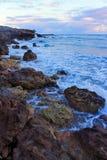 Vue des pierres et des vagues avec la mousse à une côte rocheuse de mer le soir Photographie stock libre de droits