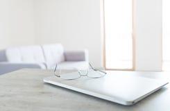 Vue des verres se trouvant sur l'ordinateur portable moderne avec l'intérieur scandinave de conception Images stock