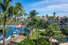 Vue du balcon du ` s d'hôtel sur une piscine tropicale entourée par des palmiers Image stock