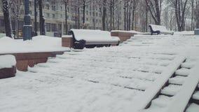 Vue du banc et des escaliers enterrés sous la neige dans le parc de Moscou banque de vidéos