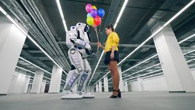 Vue du côté incliné d'un cyborg acceptant des ballons d'une dame clips vidéos